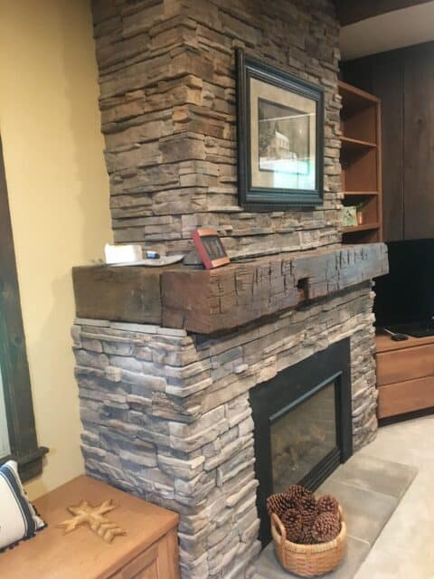 flat stone fireplace surround with hand scraped wood mantle and gas insert